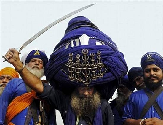 A Nihang, or Sikh warrior, Babe 'Balwant' Singh, wears a 700 meter long  and 60 kilograms (132 pounds) turban as he poses for photographs in Amritsar, India. (AP Photo) ** INDIA OUT **